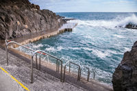 Stone pavement with railings descent to sea.