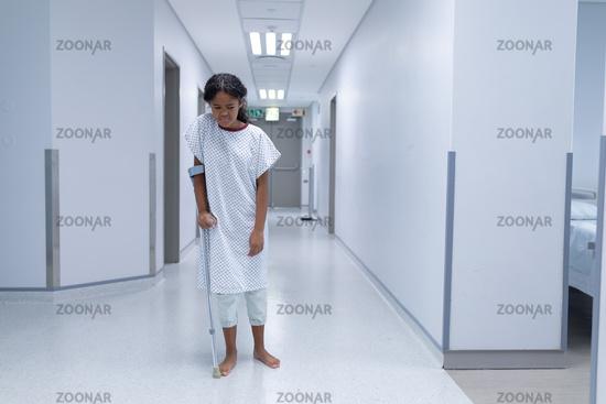 Sick mixed race girl walking barefoot in hospital corridor using a crutch