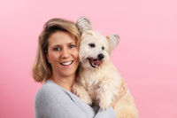 Happy woman with small dog in front of pink background