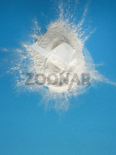 Measuring spoon with protein powder on a blue background, nutritional supplement and healthy diet