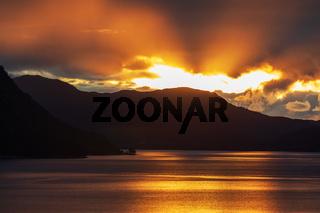 Sonnenuntergang mit dunklen Wolken und Sonnenstrahlen im Storfjord