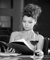 Beautiful girl reading menu in restaurant