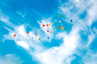 Colored flying balloons with greeting cards against blue sky background.