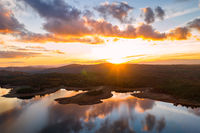Drone aerial view of a lake reservoir of a dam with perfect reflection on the water of the sunset in Sabugal, Portugal