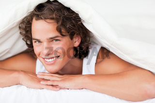 Man under a duvet with a knowing smile