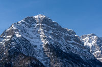 A steep and rugged mozntain face covered in snow under a blue sky in the Alps of Switzerland