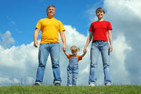 happy family stand on green grass under sky