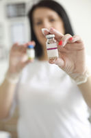 Crop beautician showing vial with anti aging serum