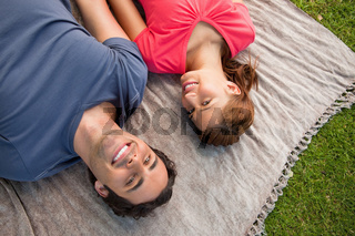 Two friends looking towards the sky while lying on a quilt