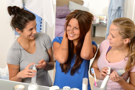 Three laughing teenager girls talking in bathroom