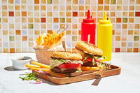 Delicious homemade burgers on wooden tray in bright sunlight. Burgers with veal cutlet, pamidor, cheese, red onion, lettuce, arugula and fries. Fast food concept