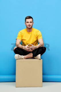 Handsome hipster man sitting on cube at studio