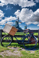 Bicycle with windmill and blue sky background. Scenic countryside landscape close to Amsterdam in the Netherlands.