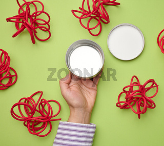 female hand holds empty white iron jar for cosmetics. Packaging for cream, gel, serum, advertising and product promotion