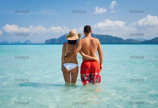 Romantic couple in love hugging on tropical beach enjoying warm ocean water