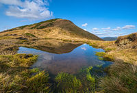 Small picturesque lake with clouds reflections at the  Strymba Mount. Beautiful autumn day in Carpathian Mountains near Kolochava village, Transcarpathia, Ukraine.