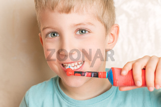 Little child smiling and brushing her teeth close up