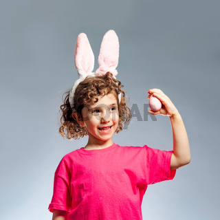 the cheerful little girl with bunny ears holding Easter egg
