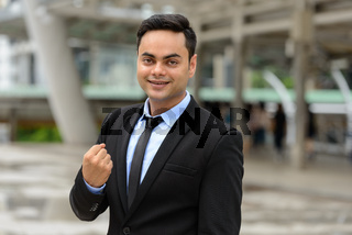 Young handsome Indian businessman in the city