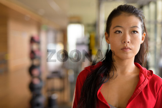 Portrait of beautiful young Asian woman thinking at gym