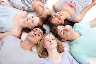 Teens sleeping on floor with heads together