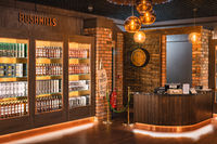Bushmills whiskey on illuminated shelfs on a display and cash register in distillery visitor centre and shop
