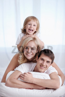 Attractive family in their pajamas on the bed