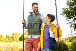 happy smiling father and son fishing on river