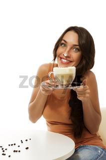 fröhliche junge frau mit einem glas cappuccino hat milchschaum auf ihrer nase