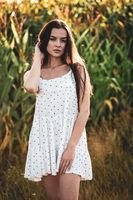 Young beautiful woman in white dress in corn field.