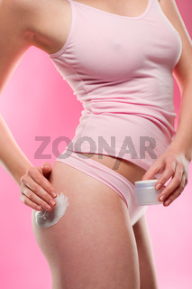 Woman in underwear apply cellulite cream bottom