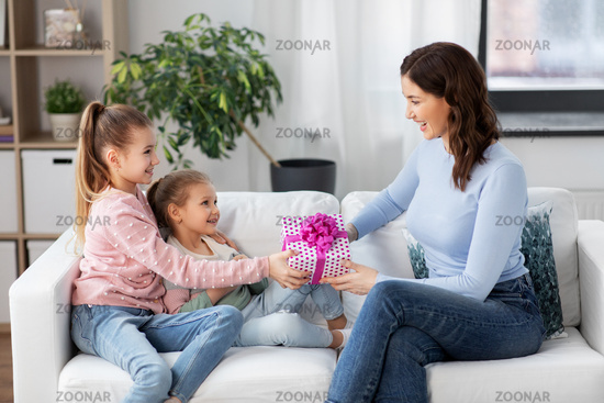 daughters giving present to happy mother