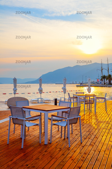 Open air cafe near the sea at sunset