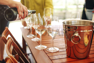 Glasses with different types of wine and human hands holding wine glasses in the background