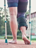 Woman walks with knee brace after an injury by medical sticks
