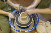 Earthenware on a potter's wheel and the hands of a potter, blurred in motion. Pottery training.