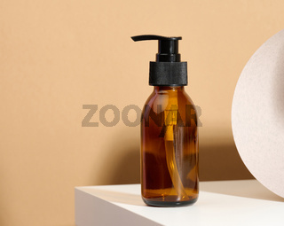 Brown glass bottle with black pump of cosmetic products on white table. Natural organic spa cosmetic, beauty concept. Mockup