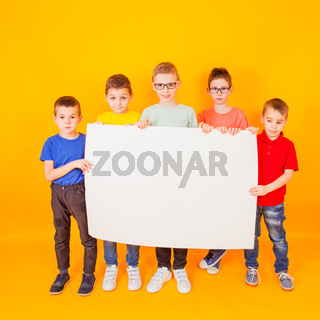 The different little boys are holding a big white paper