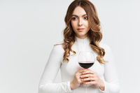 Pretty fashion woman holding glass of red wine on white background