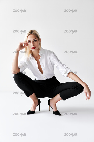 Portrait of daring trendy woman posing on white studio background.
