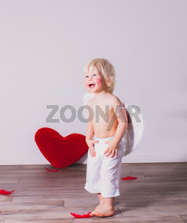 the cheerful toddler boy is having fun on Valentine's day