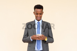 Portrait of handsome African businessman using phone against plain background