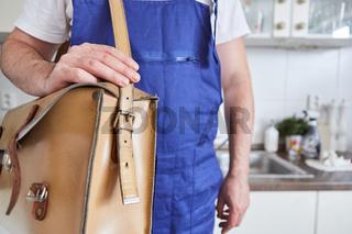 Handwerker mit Werkzeugtasche in der Küche