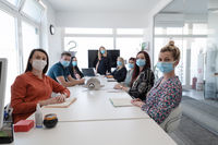 real business people on meeting wearing protective mask