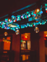Festive luminous incandescent colored lamps hanging in evening twilight in form of garland on wires