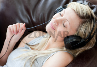 Relaxed woman with headphones on lying on a sofa
