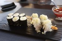 Japanese rolls sushi with cucumbers and shrimps fried on black plate