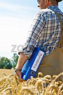 Bauer mit Mappe 'Förderung' auf Getreidefeld