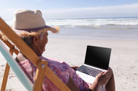 Senior african american woman holding laptop while sitting on deck chair at the beach