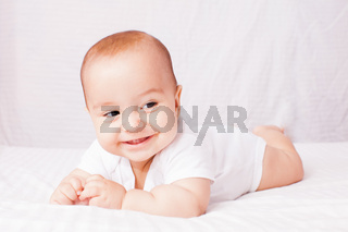 happy baby lying on white bed and smile
